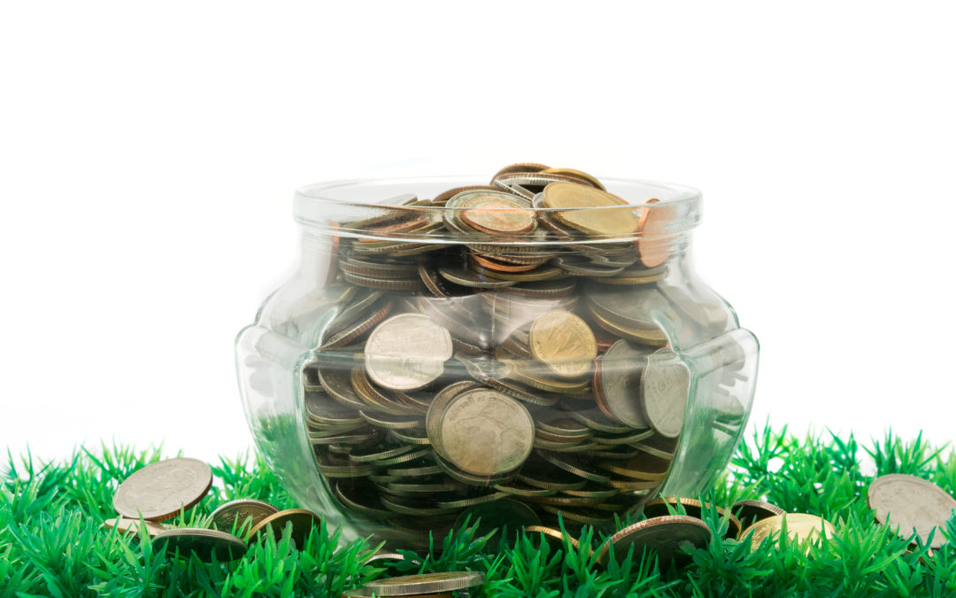 glass jar full of bath coins on artificial grass on white background